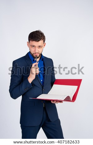 Young businessman thinking with a folder and pen