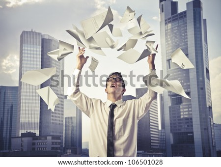 Young businessman throwing some paper sheets in the air with cityscape in the background - stock photo