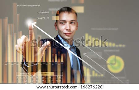 Young businessman touching icon of media screen with diagrams and graphs - stock photo