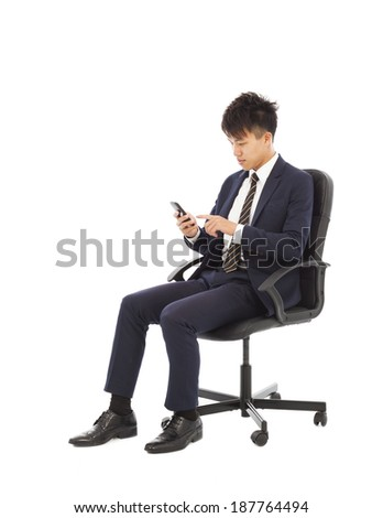 young businessman touching smart phone on chair