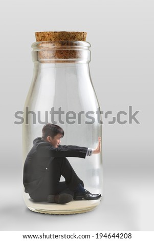 Young businessman trapped in a glass jar - stock photo