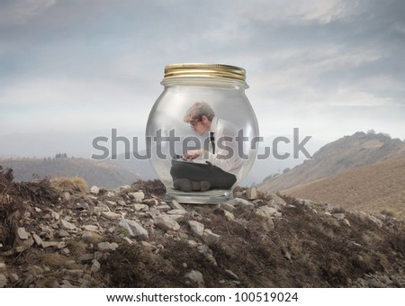 Young businessman trapped in a glass jar and using a laptop on a mountain peak - stock photo