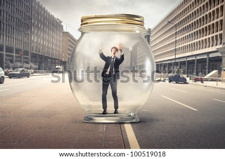Young businessman trapped in a glass jar in the middle of a city street - stock photo