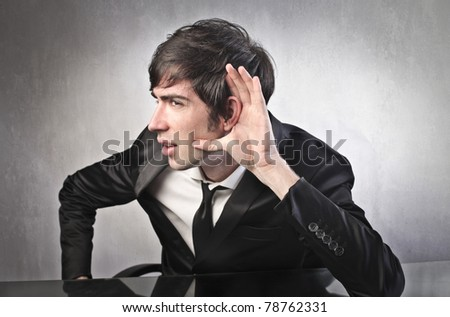 Young businessman trying to listen to something
