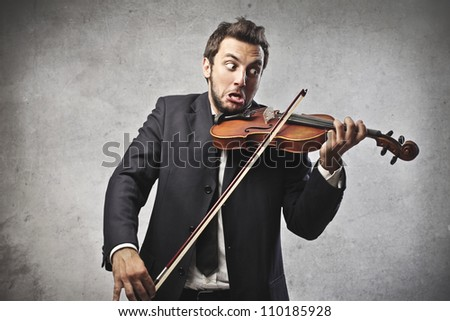 Young businessman trying to play the violin - stock photo