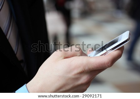 Young businessman typing with cellphone - stock photo