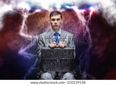Young businessman under rain sitting on chain - stock photo
