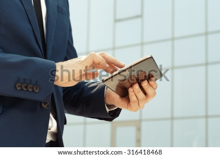 Young businessman using a digital tablet outdoors - stock photo