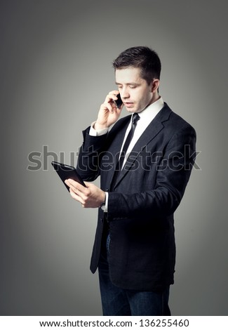 young businessman using a digital tablet speaks on the phone