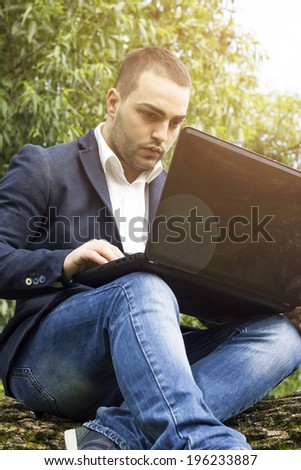 Young businessman using a laptop pc computer while sitting on a  tree outdoors.