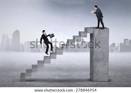 Young businessman using a megaphone for commanding his employee to meet with him - stock photo