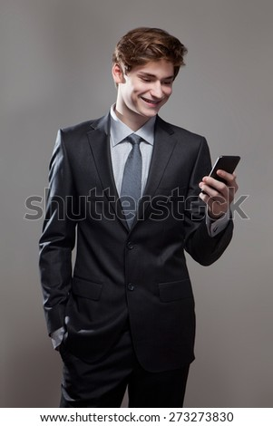 Young businessman using a mobile phone, on gray background - stock photo