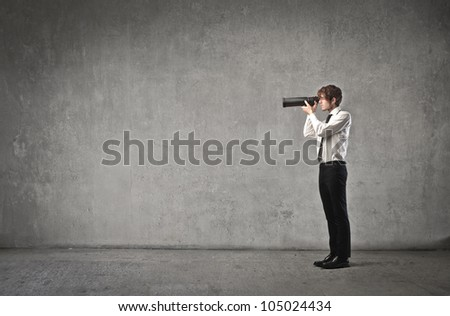 Young businessman using a telescope - stock photo