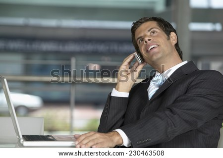Young Businessman Using Cell Phone and Laptop - stock photo