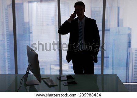 Young businessman using cell phone at office desk - stock photo