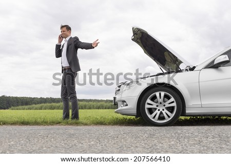 Young businessman using cell phone by broken-down car at countryside - stock photo