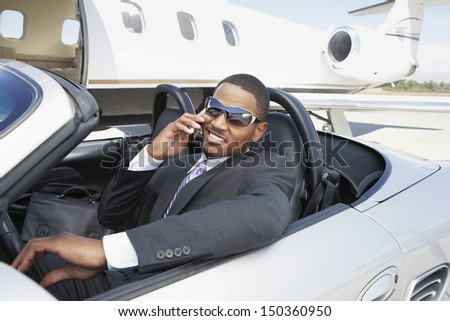 Young businessman using cell phone in convertible near private jet - stock photo