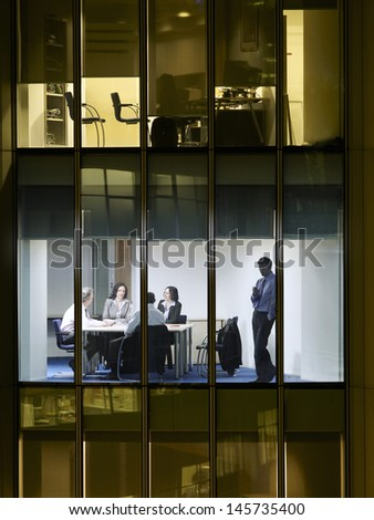 Young businessman using cellphone with colleagues discussing in conference room at night - stock photo