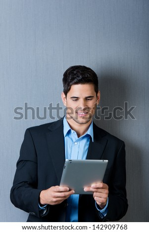 Young businessman using digital table against blue wall - stock photo
