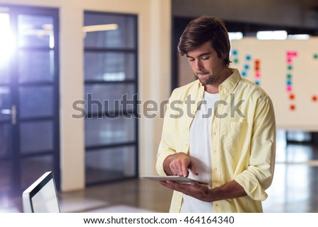 Young businessman using digital tablet in creative office