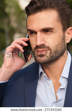 Young businessman using his mobile phone on the park - stock photo