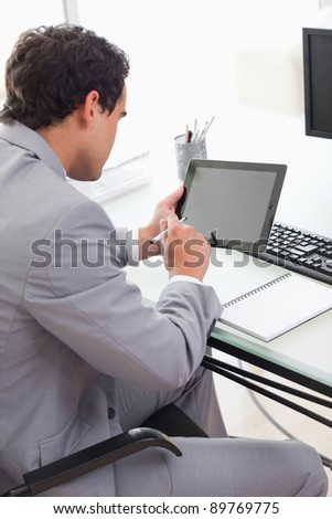 Young businessman using his tablet in his office