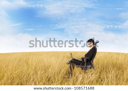 Young businessman using laptop computer to work on the meadow. shot outdoor