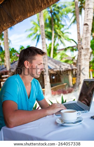 Young businessman using laptop during summer tropical vacation - stock photo