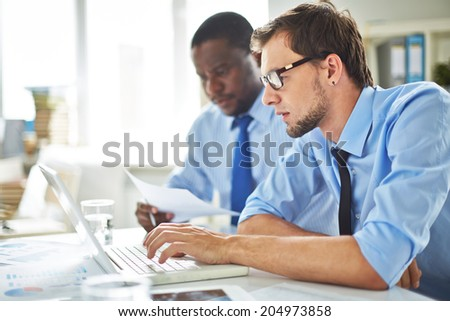 Young businessman using laptop on background of his partner reading paper - stock photo
