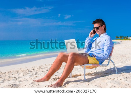 Young businessman using laptop on tropical beach - stock photo
