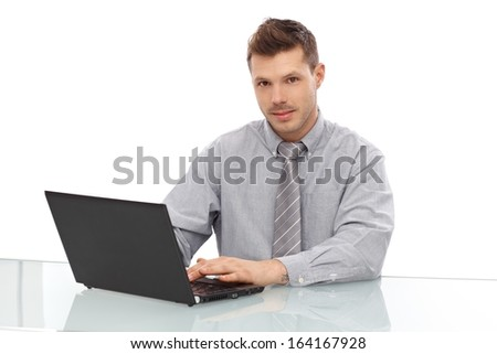 Young businessman using laptop, sitting at desk.