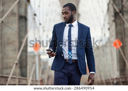 Young businessman using mobile phone on Brooklyn Bridge. New York City.
