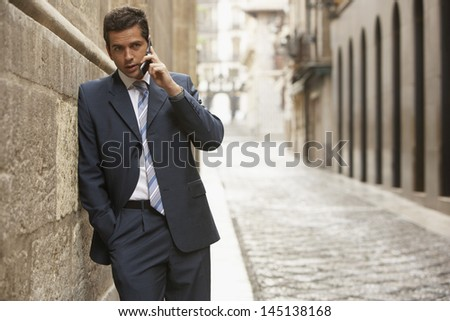 Young businessman using mobile phone while leaning on wall in street