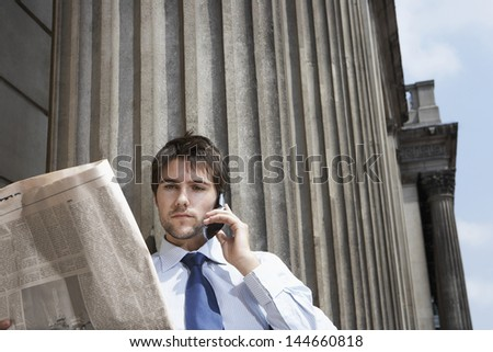 Young businessman using mobile phone while reading newspaper outside building - stock photo