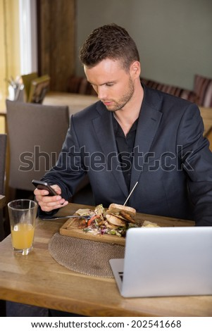 Young businessman using mobilephone while having food in cafe