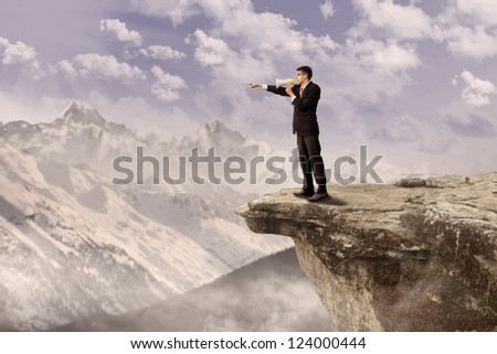 Young businessman using speaker on top of a high mountain - stock photo