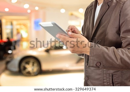 Young BusinessMan using Tablet device with Modern Sportcar as Modern Lifestyle Concept.  Selective Focus on Right hand Trigger finger . - stock photo