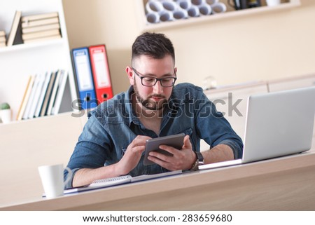 Young businessman using tablet in his office
