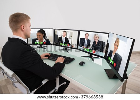 Young Businessman Video Conferencing On Desk With Multiple Computers - stock photo