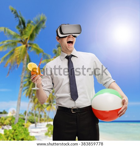 Young businessman visualizing a beach environment using a VR headset and holding a cocktail and a beach ball shot with tilt and shift lens - stock photo