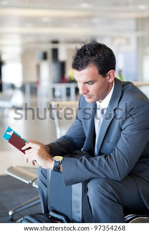 young businessman waiting for his flight in airport - stock photo