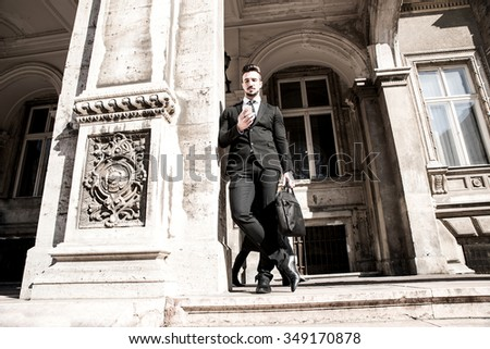 Young businessman waiting outside on the street, using his smartphone