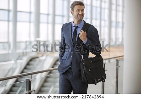 Young businessman walking at the airport with briefcase smiling - stock photo