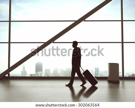young businessman walking in airport with bag - stock photo