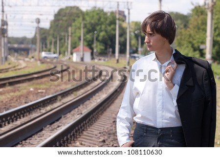 young businessman walking near the railroad - stock photo