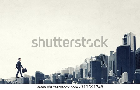 Young businessman walking on buildings roofs representing success concept - stock photo