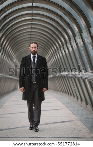 Young businessman walking on futuristic pedestrian bridge at the Defense District. Paris, France.