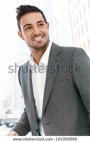 Young businessman walking on street in downtown, looking away, smiling. - stock photo