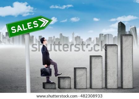 Young businessman walking on the rising sales graph with sales word on the signpost