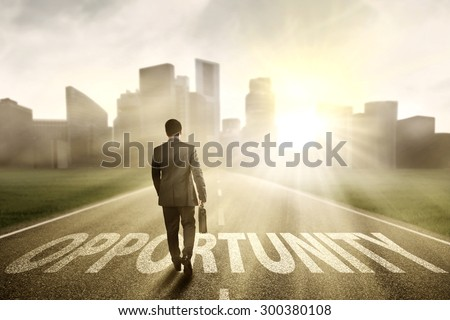 Young businessman walking on the road to new opportunity in the morning at a city - stock photo